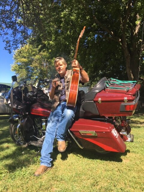 pic of me with a guitar and a cigar leaning on my bike
