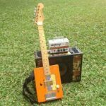 pic of six string CBG with Fender type head stock and cigar box amp